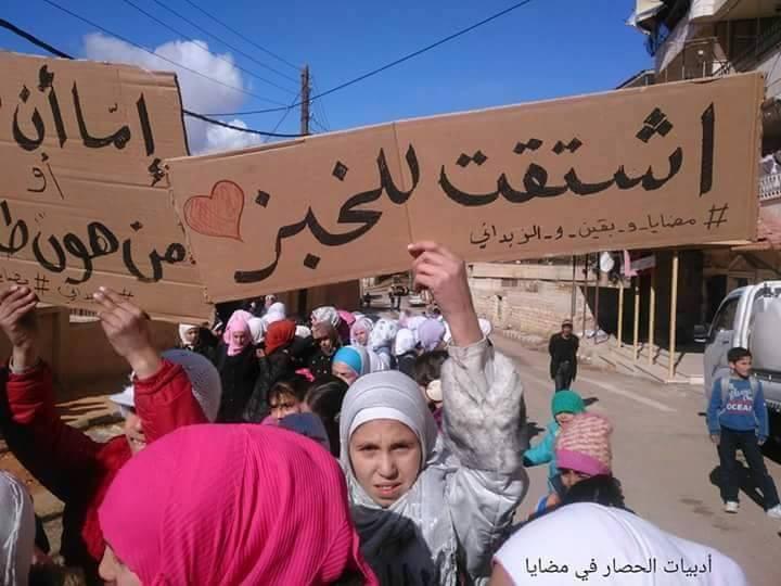 На демонстрации девочка держит плакат - соскучилась по хлебу